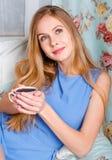 Mooie jonge blonde vrouwenzitting op een laag, holding een kop van Stock Afbeeldingen