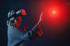 Mooie jonge blondevrouw die een VR-glazen wat betreft denkbeeldig voorwerp in lucht draagt tijdens de virtuele werkelijkheidserva royalty-vrije stock foto