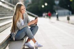Mooie jonge blondevrouw die haar smartphone en smili bekijken royalty-vrije stock afbeelding