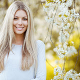 Mooie jonge blondevrouw die zich dichtbij de appelboom bevinden stock afbeelding