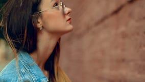 Mooie jonge blondevrouw met rode lippen die bij de bakstenen muur stellen