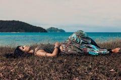 Mooie jonge bohovrouw die op een gras bij het strand liggen stock foto