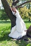 Mooie jonge bruid die tegen een boom wordt geleund Royalty-vrije Stock Afbeeldingen