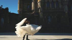 Mooie jonge bruid en knappe bruidegomholding in de lucht in openlucht dichtbij oud herenhuis stock footage