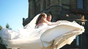 Mooie jonge bruid en knappe bruidegomholding in de lucht in openlucht dichtbij oud herenhuis stock videobeelden