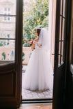 Mooie jonge bruid in huwelijkskleding een leuk boeket houden die zich bevindt op het balkon van de uitstekende bouw Stock Foto