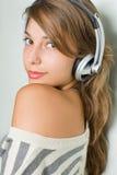 Mooie jonge brunette die hoofdtelefoons draagt Royalty-vrije Stock Afbeeldingen