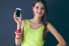Mooie jonge cellphone van de vrouwenholding, die zich dichtbij donkere muur bevinden Royalty-vrije Stock Foto's