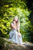 Mooie jonge dame die elegante witte kleding dragen die van de stralen van hemellicht op haar gezicht in verrukt hout genieten. Moo Royalty-vrije Stock Foto's