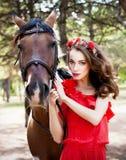 Mooie jonge dame die rode kleding dragen die een paard berijden bij zonnige de zomerdag Brunette met lang krullend haar met bloem Stock Foto