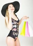 Mooie jonge dame in een badpak, grote zwarte hoed op hoge hielen die, die kleurrijke zakken houden en op de telefoon spreken Stock Afbeelding