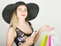 Mooie jonge dame in een badpak, grote zwarte hoed op hoge hielen die, die kleurrijke zakken houden en op de telefoon spreken Stock Fotografie