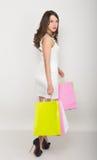 Mooie jonge dame in een weinig witte kleding op hoge hielen, die kleurrijke zakken houden Het meisje gaat winkelend Stock Afbeeldingen