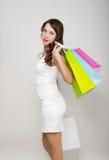 Mooie jonge dame in een weinig witte kleding op hoge hielen, die kleurrijke zakken houden Het meisje gaat winkelend Royalty-vrije Stock Fotografie