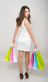 Mooie jonge dame in een weinig witte kleding op hoge hielen, die kleurrijke zakken houden Het meisje gaat winkelend Stock Foto's