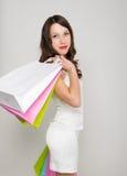 Mooie jonge dame in een weinig witte kleding op hoge hielen, die kleurrijke zakken houden Het meisje gaat winkelend Royalty-vrije Stock Foto