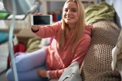 Mooie jonge dame in roze hoodie die moderne cellphone houden royalty-vrije stock fotografie