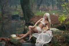 Mooie jonge damezitting dichtbij rivier in verrukt hout Sensueel blonde met witte kleren die provocatively in herfstpark stellen Stock Foto's