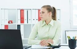 Mooie jonge die secretaresse in gedachte bij het werk in het bureau wordt verloren Stock Afbeelding