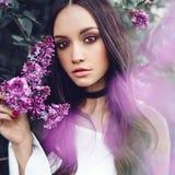 Mooie jonge die vrouw door bloemen van sering wordt omringd royalty-vrije stock fotografie