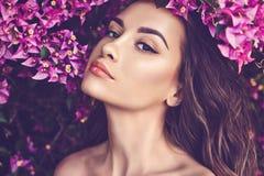 Mooie jonge die vrouw door bloemen wordt omringd royalty-vrije stock foto