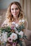Mooie jonge die vrouw in een huiskleding in het boudoir, met mooie bloemen wordt verfraaid, die op een wit bed met een luifel zit Stock Afbeeldingen