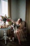 Mooie jonge die vrouw in een huiskleding in het boudoir, met mooie bloemen wordt verfraaid, die op een wit bed met een luifel zit Stock Afbeelding
