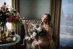 Mooie jonge die vrouw in een huiskleding in het boudoir, met mooie bloemen wordt verfraaid, die op een wit bed met een luifel zit Royalty-vrije Stock Foto