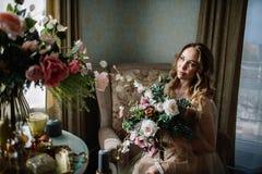 Mooie jonge die vrouw in een huiskleding in het boudoir, met mooie bloemen wordt verfraaid, die op een wit bed met een luifel zit Royalty-vrije Stock Afbeelding