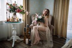 Mooie jonge die vrouw in een huiskleding in het boudoir, met mooie bloemen wordt verfraaid, die op een wit bed met een luifel zit Royalty-vrije Stock Fotografie