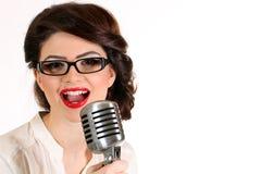 Mooie jonge die vrouw op wit in studio in oude manierkleren die pinup en retro stijl met microfoon wordt geïsoleerd vertegenwoord Stock Foto