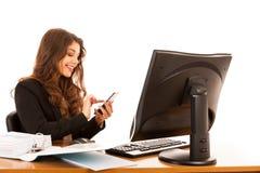Mooie jonge donkerbruine bedrijfsvrouw surt Internet op haar lusje Royalty-vrije Stock Afbeelding
