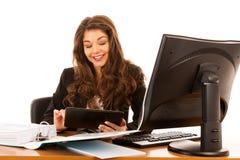 Mooie jonge donkerbruine bedrijfsvrouw surt Internet op haar tablet in bureau stock fotografie