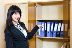 Mooie jonge donkerbruine vrouw die aan omslagen met documenten tonen Stock Foto's