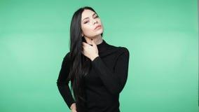 Mooie jonge donkerbruine vrouw in het zwarte overhemd spelen met het haar stock video