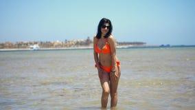 Mooie jonge donkerbruine vrouw in zonnebril en het heldere oranje zwempak stellen voor de camera, op het strand stock footage