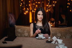Mooie jonge donkerbruine vrouwenzitting in een koffie Stock Afbeelding