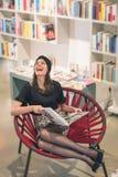 Mooie jonge donkerbruine zitting in een boekhandel royalty-vrije stock afbeeldingen