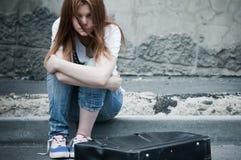 Mooie jonge droevige meisjeszitting op asfalt Royalty-vrije Stock Afbeelding