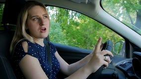 Mooie jonge en vrouw die terwijl het drijven van auto op plattelandsweg dansen zingen stock video