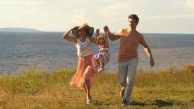Mooie jonge familie die langs de klip op de achtergrond van de rivier en de zon lopen stock footage