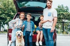 mooie jonge familie met hond die zich naast klaar auto bevinden royalty-vrije stock afbeeldingen