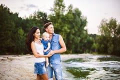 Mooie jonge familie op vakantie met baby De vader houdt het blondemeisje in haar wapens, en de donkerbruine moeder van ` s koeste royalty-vrije stock afbeelding