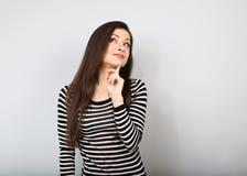 Mooie jonge gelukkige vrouw met vinger onder het en gezicht die omhoog denken eruit zien stock afbeeldingen