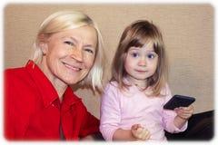 Mooie jonge glimlachende blondegrootmoeder en weinig leuke kleindochter stock fotografie