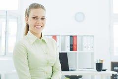 Mooie jonge glimlachende onderneemster op de achtergrond van haar bureau Stock Afbeelding