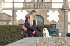 Mooie jonge het glimlachen meisjeswandelingen met kleine witte hond Duitse dwergspitz pomeranian royalty-vrije stock foto's