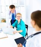 Mooie jonge het glimlachen vrouwelijke artsenzitting bij het bureau Stock Foto's