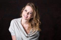 Mooie jonge het glimlachen vrouwenstudio op een donkere achtergrond royalty-vrije stock foto's