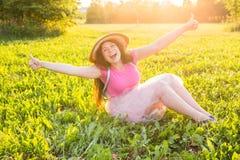 Mooie jonge het lachen ongehoorzame vrouwenzitting op het gras en het glimlachen Royalty-vrije Stock Foto's